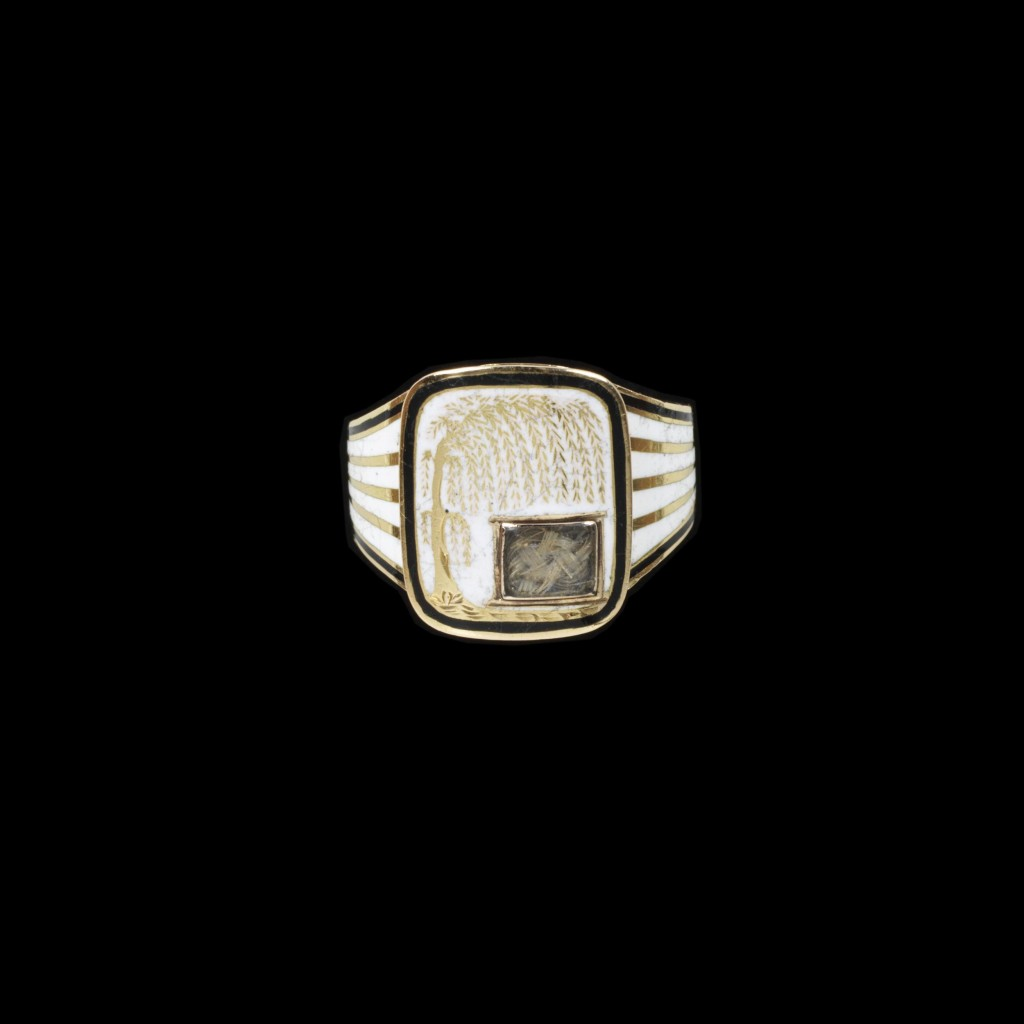 Gold mourning ring enamelled in black and white. The shaped rectangular bezel, with a willow tree reserved on white enamel with a small glazed locket containing hair. Inscribed behind Anna/ Seward./ Ob. 25 March, 1809.' Aet. 66.