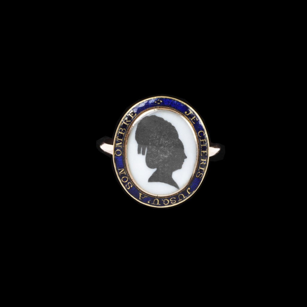 Enamelled gold ring, the oval bezel set with a silhouette of a woman with a locket of hair under the bezel. The border inscribed JE CHERIS JUSQU'A SON OMBRE. A French import mark from 1864 on the hoop.