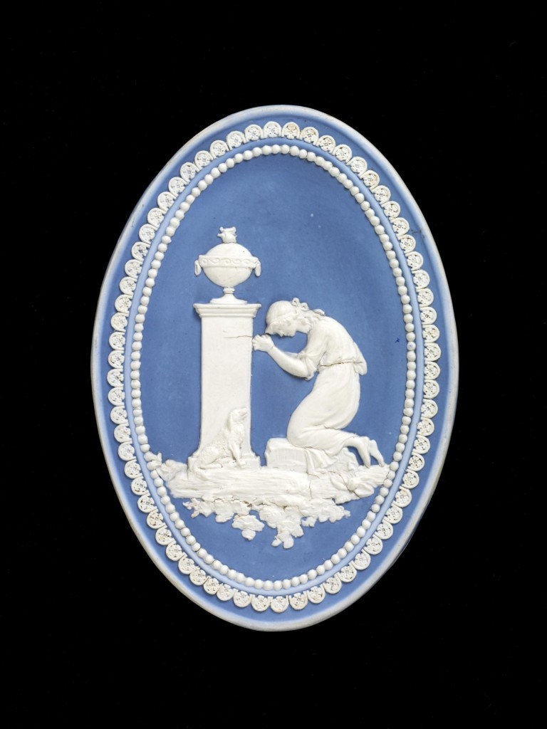 Oval plaque of white stoneware with blue jasper dip and applied white stoneware relief. The scene depicts 'Charlotte Mourning at the tomb of Werther', from a popular Romantic novel by Goethe. A female figure kneels in prayer before a pedestal on which stands an urn. She wears classical robes. At the foot of the pedestal is a seated dog. Around the outside of the scene is a border of applied white flowers, within which is another border of dots.
