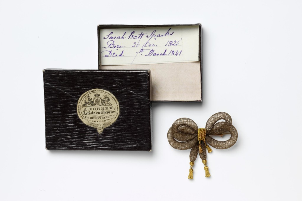 Hair-work brooch made of brown human hair. Shaped in a bow. The centre is bound round with gold wire and the ends are trimmed with gold tassels. There is a gold pin engraved with the birth and death dates of a 16-year-old. With a black card box with an engraved label.