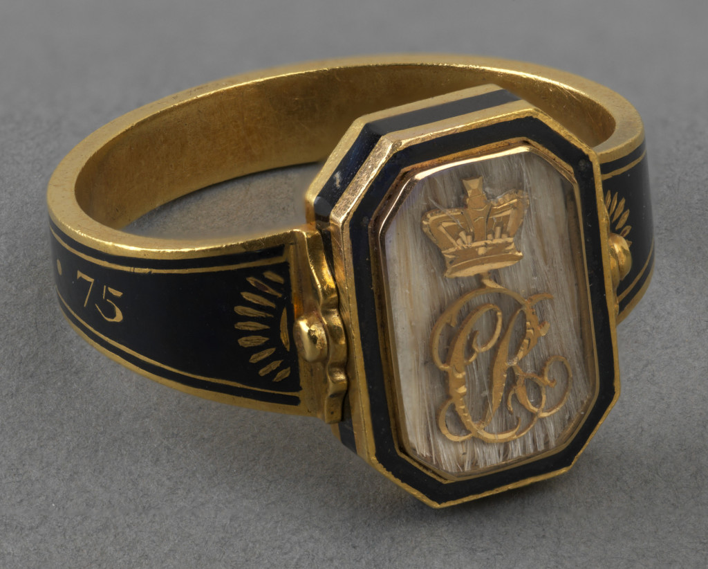 Gold and black enamel mourning ring with an octagonal swivel case containing, on one side, a gold crowned CR monogram on ground of white hair, under a crystal; the reverse with lock of grey hair and an inscription on the band 'ob 17 Nov, 1818 aet. 75'. Shank enamelled in black.