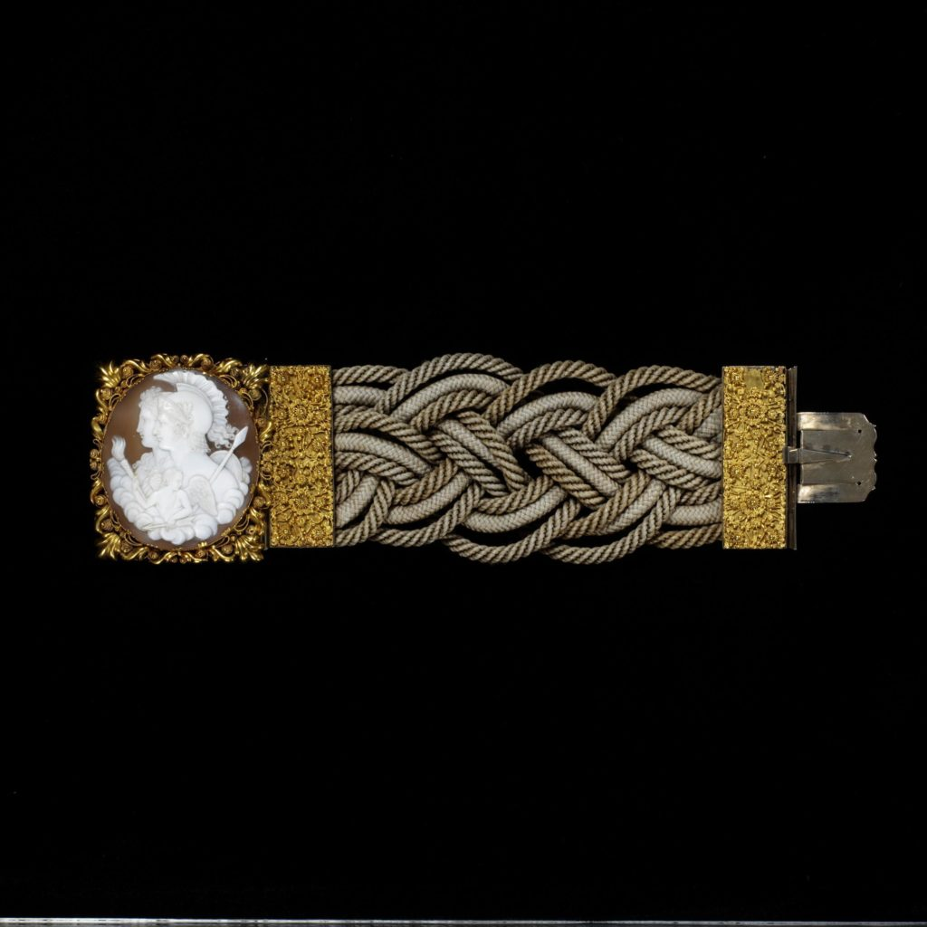 A bracelet band made from plaited and twisted human hair. The gold clasp is set with a shell cameo.The gold decorated with graniti (small applied pellets) and cannetille (wire spiral). It possibly represents Alexander the Great, his wife Roxana and a genius, or protecting deity, with a torch, c.1830-50.