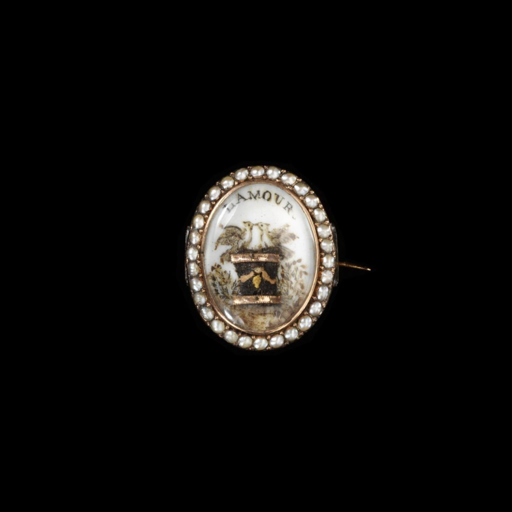 Often mass produced, this kind of jewellery bears generalised messages such as here 'L'Amour' (Love) or 'À vous dedié' (Dedicated to you). Gold set with pearls, hair and ivory painted in watercolour with applied gold foil.
