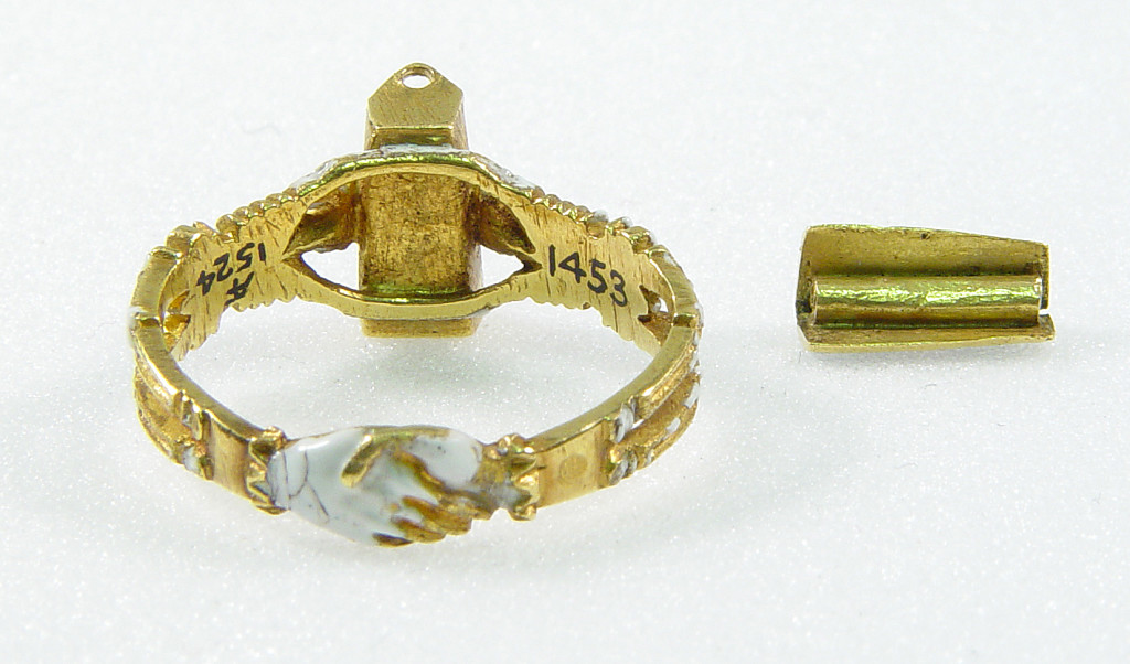 Mourning-ring; enamelled gold, the hoop enamelled white, in the form of two skeletons supporting a coffin-shaped bezel with moveable lid fastened with a pin and ornamented with a Maltese cross once enamelled red, on a black ground with hearts reserved in the metal, an enamelled cinquefoil at one end. Inside the coffin is a tiny white-enamelled skeleton. At the back of the bezel ares two clasped hands.