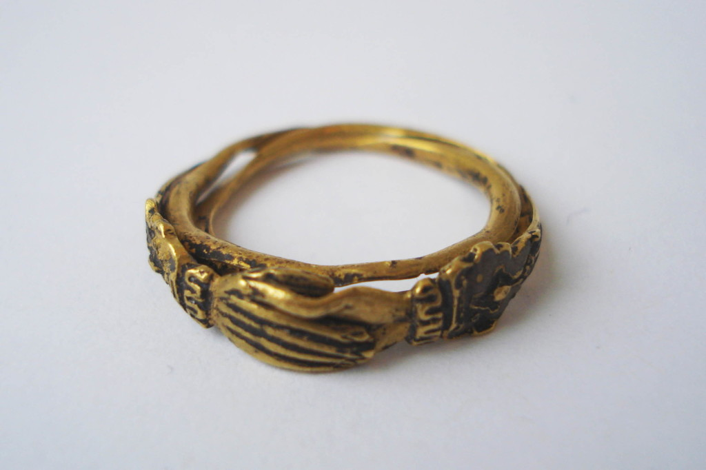 A gold fede and gimmel ring consisting of two interlocking and twisted hoops with clasped hands forming the bezel. Within the lower hand is a heart and, when the two hoops are joined, the top hand clasps this heart. The hands extend to the shoulders, becoming cuffs and these are decorated and partly enamelled. On the inside of each hoop is an inscription that remains concealed when the two hoops are shut.