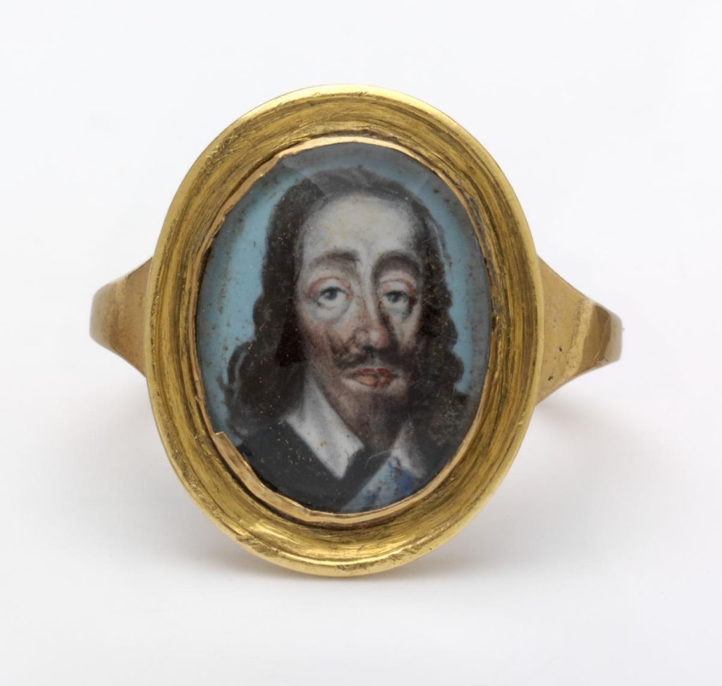 Gold commemorative ring, the oval bezel set with a crystal enclosing a miniature of Charles I.