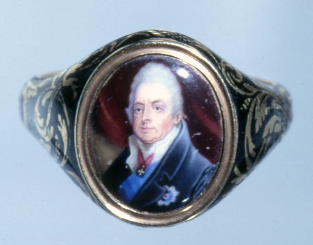 c.1817-30 mourning ring; hoop and sides of bezel ornamented with scrollwork reserved on ground of black enamel; oval bezel containing portrait bust to left of William IV as Duke of Clarence in enamel; wears dark blue coat with star and ribbon of the Garter, and badge of the Order of the Bath; inscribed.