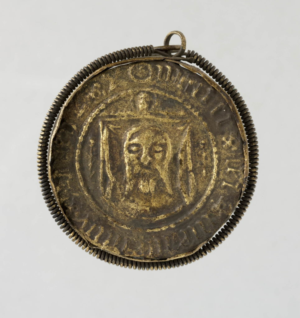 Pilgrim-badge; brass; circular; set in rim, round which is scroll of twisted wire and suspension loop; embossed with representation of St Veronica holding out the Vernicle