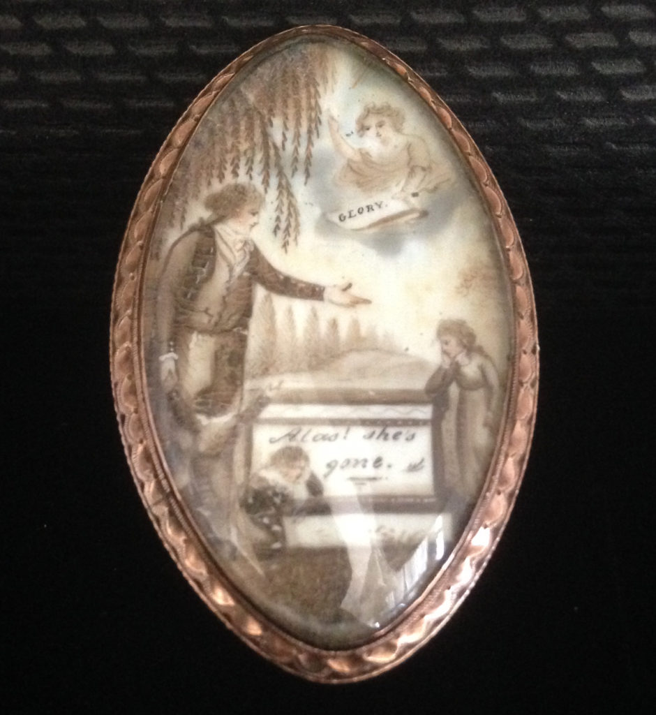 Neoclassical mourning jewel showing father and children next to a tomb inscribed 'Alas! She's gone'. In the Heavens is a cherub holding a sign stating 'GLORY'.