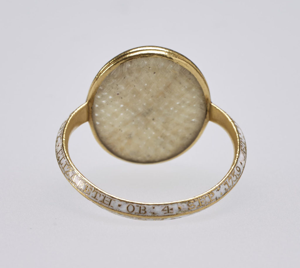 Small gold mourning ring, the centre set with oval crystal containing woven hair and carved with intaglio profile head of Princess Elizabeth, sister of George III, facing right. Inscription on band reads, 'LADY ELIZABETH.OB.FOR.SEP.1759 AET. 18.EN MEMOIRE D'UNE AMITIE CHERE.'