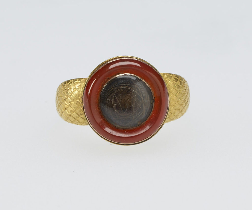 A gold mourning ring chased with diaper pattern. The circular top set with cornelian rim, encircling crystal with hair. Provenance Bequeathed to Princess Elizabeth by her sister Princess Sophia Matilda of Gloucester; on her own death in 1844.