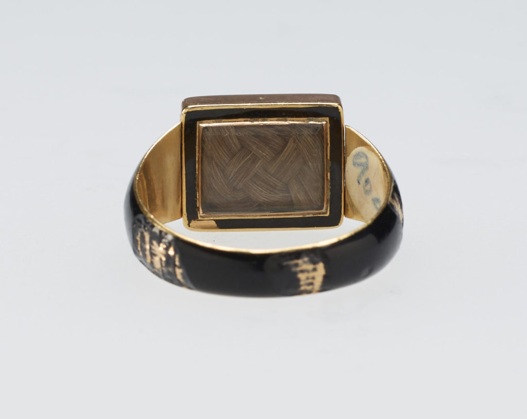 Mourning ring for Georgiana, Duchess of Devonshire (1757-1806). Gold ring, hoop enamelled in black with central hinged rectangular reserve, set with bloodstone carved with ducal coronet above gothic GD monogram and inscription, 'ob. March 30 / 1806'. Back set with woven hair behind glass.
