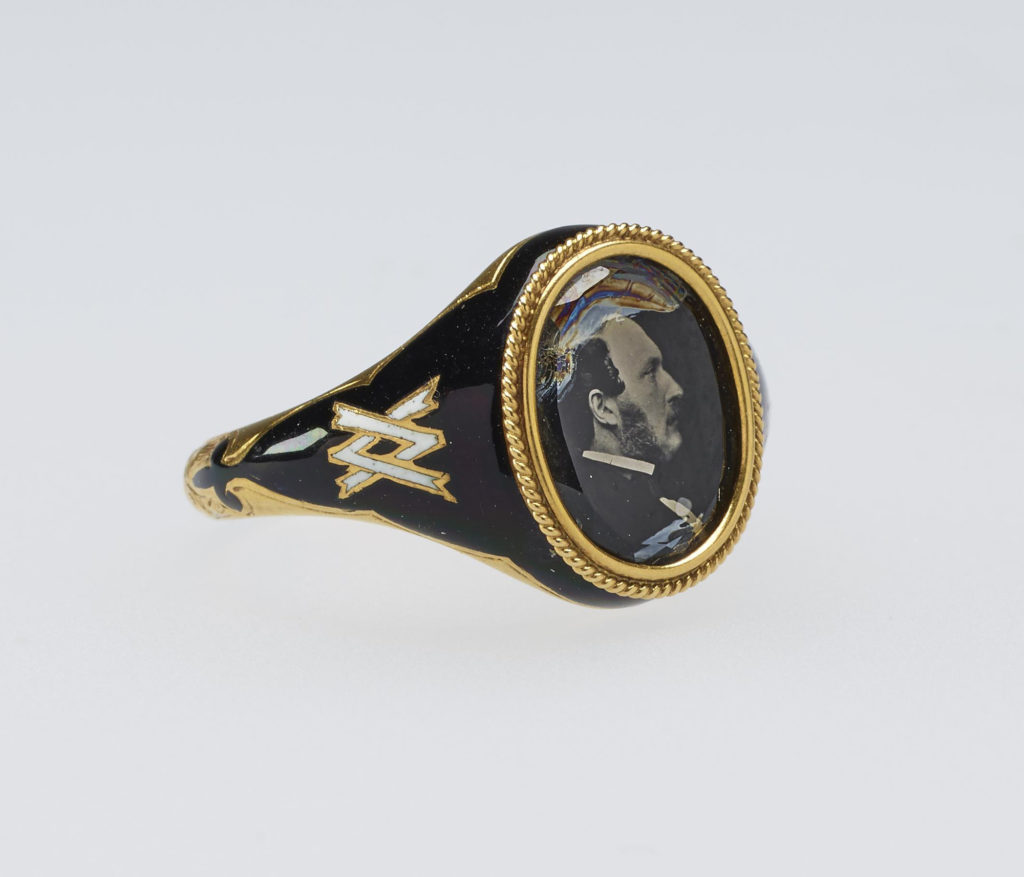 Queen Victoria's memorial ring in gold and black enamel, the bezel containing a microphotograph, reversed, of the Prince Consort in 1861, which is attributed to J.J.E. Mayall. The cypher linking the initials 'V' and 'A' in white enamel is set into the shanks on either side of the bezel.